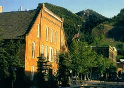 Aspen City Hall - a brick building in the foreground of forested mountains